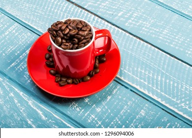 An espresso cup full of coffee beans on a weathered table