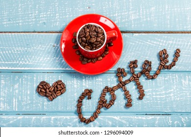 An espresso cup full of coffee beans on a weathered table with the word coffee and a heart