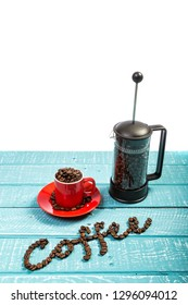 An espresso cup full of coffee beans and a cafeteria on a weathered table with the word coffee spelt out