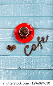 An espresso cup full of coffee beans on a weathered table with the word cafe and a heart spelt out