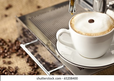 Espresso cup full with coffee beans. In background are more coffee beans visible.
