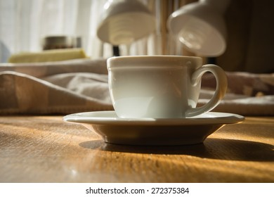Espresso cup on a wooden table in the sunlight