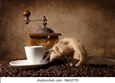 espresso cup surrounded by coffee beans and a vintage grinder