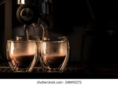 Espresso machine brewing a coffee, double wall glass.