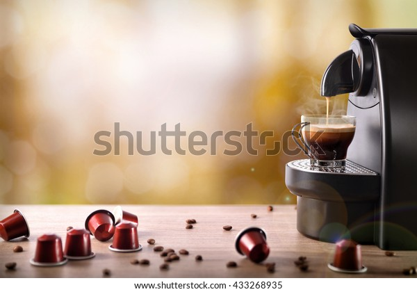 Espresso machine making coffee with capsules on wood table. Front view