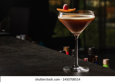 Espresso Martini Cocktail based on coffee, liqueur and vodka. Served with orange chips and raspberry. Space for text