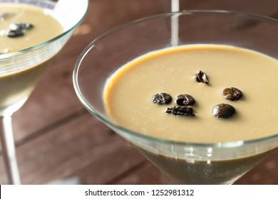 Espresso Martini Cocktail, vodka, kahlua, espresso coffee, in a Martini glass on wooden table. Close up