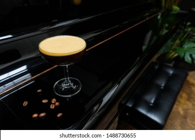 """""""Espresso Martini"""" new menu by using double shot of espresso with syrup and shake serving glass on the black classic piano"""