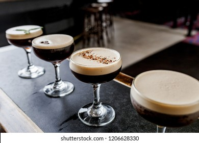Espresso martinis with different garnishes lined up on a bar.