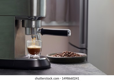 Espresso oozes out of home coffee and fills a beautiful transparent mug with two contours on the background of c serves coffee beans. Consumer electronics for the kitchen.