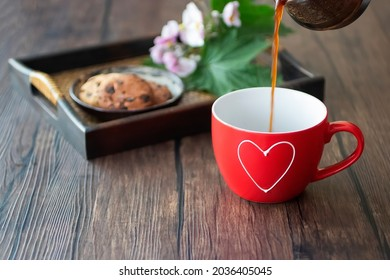 Espresso is poured into a red cup on a brown tray on a brown wooden table. Soft focus.