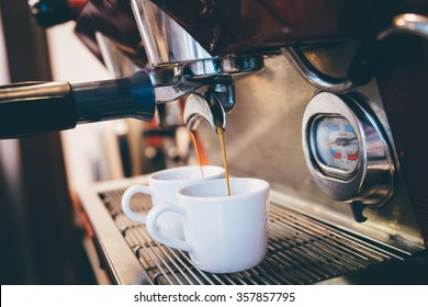 Espresso pouring from coffee machine, close up, professional coffee brewing. Espresso machine making coffee in pub, bar, restaurant