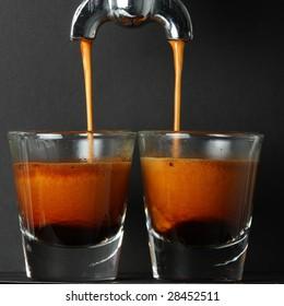 Espresso pouring into two shot glasses