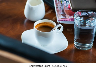 Espresso set, smart phone, magazines on a working table. Break time, office work concept.
