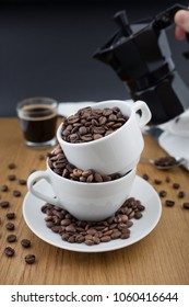 Espresso shot, coffee beans in the cup and coffee percolator on wooden table with black background