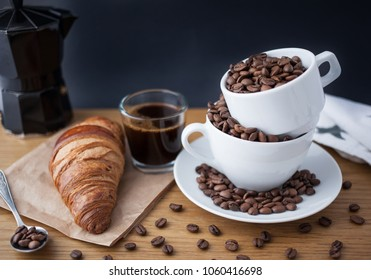 Espresso shot, coffee beans in the cup, coffee percolator and croissant on wooden table with black background
