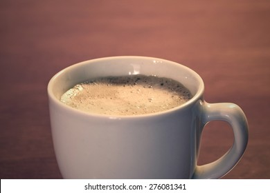 Espresso in a white cup on a wooden background
