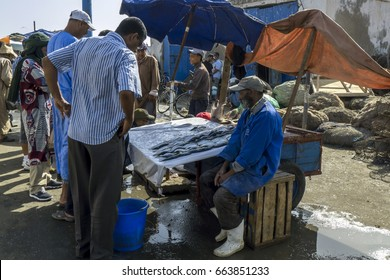 ESSAOUIRA, MOROCCO - AUGUST 01, 2013 : A fish monger at work at the busy fishing port of Essaouira in Morocco. The present city of Essaouira was built during the 18th century.