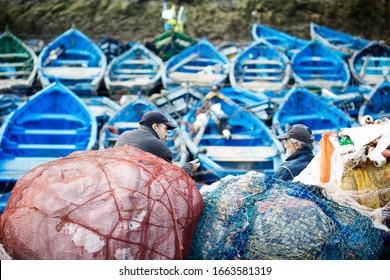 Essaouira, Morocco - February 17 2020 Men fishermen on blue fishing boats.