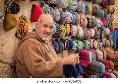 ESSAOUIRA, MOROCCO - MARCH 01, 2017: A pleasant man making and selling hats and in Essaouira, Morocco.