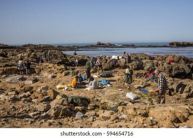 ESSAOUIRA, MOROCCO - NOVEMBER 17, 2016: Fishermen on the beach. Mussel catchers on the beach dry their clothes and nets on November 2016 in Essaouira, Morocco