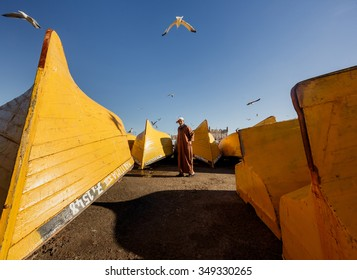 ESSAOUIRA, MOROCCO - NOVEMBER 4, 2015: Unidentified fisherman in front of yellow boats in the port on the coast of Essouira, Morocco.