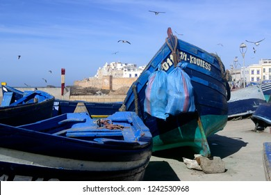 Essaouira, Morocco - October 15, 2018: Seagulls flying over blue fishing boats in the port with the old city walls in the background