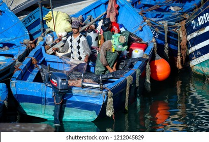 Essaouira, Morocco - October 2, 2018: Fishermen are preparing nets and other gear in a wooden blue Maroccan fishing boats in Essaouira city port harbor