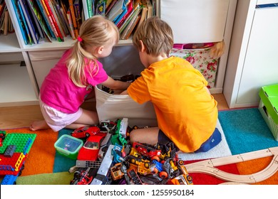 ESSEN / GERMANY - JUNE 26 2018 : Brother and Sister tidying up the colorful chaos in the kids room