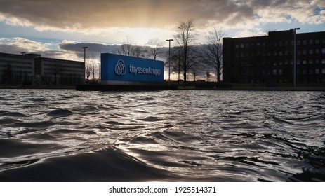 Essen, NRW, Deutschland, 02-26-2021 Thyssen krupp company logo in moving Water against sundown - headquarters Thyssen krupp AG, based in Essen, is a listed, diversified industrial group