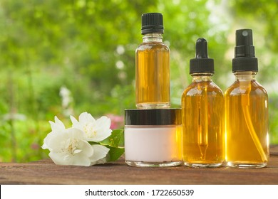 Essence of flowers on a wooden background in a beautiful glass jar