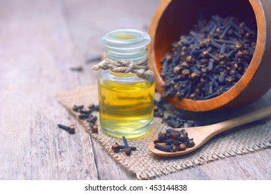 Essential aroma clove oil in a glass bottle with dried cloves on wooden spoon and  background.