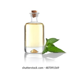 Essential aroma oil in glass bottle with fresh mint leaves on white background