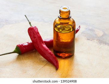Essential aroma oil from hot peppers on wooden background. Selective focus.