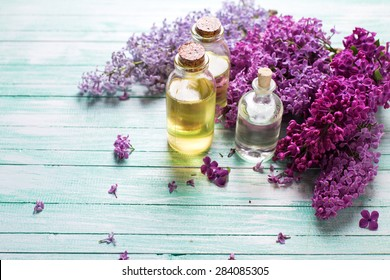 Essential aroma oil with lilac on  turquoise painted wooden background. Selective focus. Place for text.