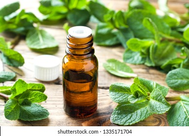 Essential aroma oil with peppermint on wooden background. Selective focus, copy space