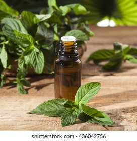 Essential aroma oil with peppermint on wooden background. Selective focus, horizontal.
