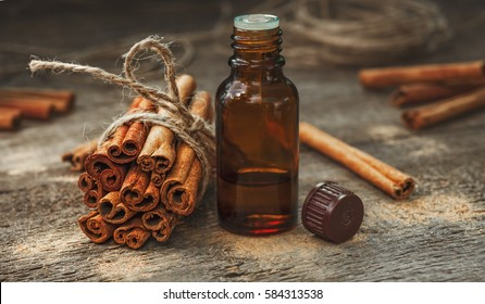 Essential cinnamon oil in a small bottle, ground cinnamon and cinnamon sticks on old wooden background
