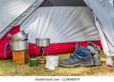 Essential cooking equipment in front of a colorful tent on a campsite