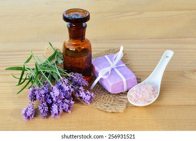 Essential lavender oil, fresh lavender flowers, soap and bath salts on wooden background.
