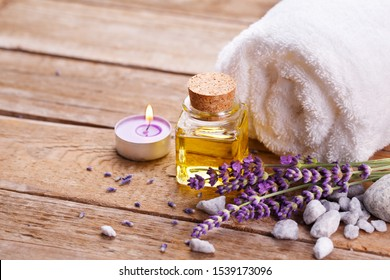 Essential lavender oil in glass bottle with lavender flowers, candle and towel on rustic wood -  Spa and wellness background