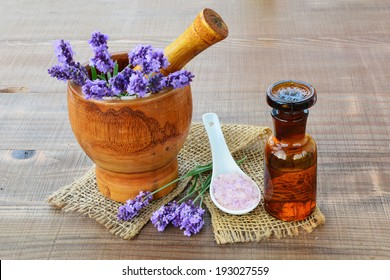 Essential lavender oil, wooden mortar with fresh lavender flowers, bath salts on wooden background.
