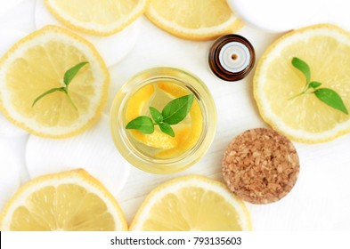 Essential lemon oil, dropper bottle, jar of homemade extracted skincare lotion, fresh yellow citrus fruit slices viewed from above.
