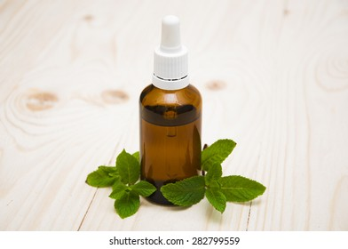 Essential mint oil with fresh mint on a old wooden background