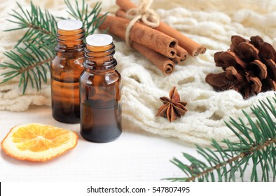 Essential oil blend. Dark glass bottles, cinnamon, pine twigs, dried citrus slice, anise, woolen wrap. Natural home deodorants. Warm toned.