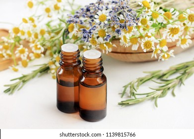 Essential oil blend with different aroma herbs: chamomile, rosemary, lavender. Fresh blossom and droppper bottles white table. Healing aromatherapy.