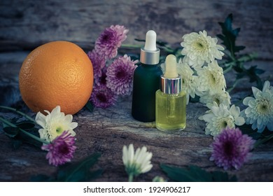 Essential oil bottle and colorful flowers frame on a wooden background. holiday concept.