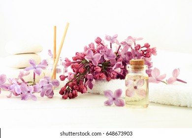 Essential oil bottle corked with flower inside in extract, fresh lilac, white light tones, botanical aromatherapy background.
