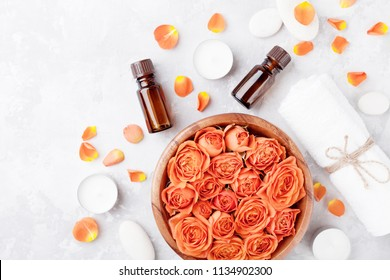 Essential oil bottle, rose flower in bowl, towel and candles on stone table top view. Spa, aromatherapy, wellness, beauty background.