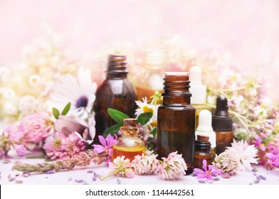 Essential oil bottles on medicinal flowers and herbs background, selective focus, toned